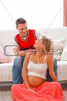 Young man making massage his pregnant wife