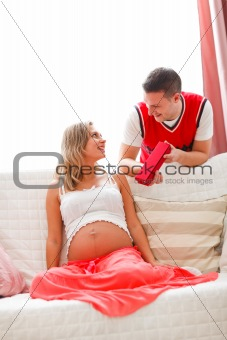 Young husband making present to pregnant wife