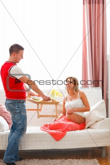 Young guy bring breakfast to happy pregnant wife