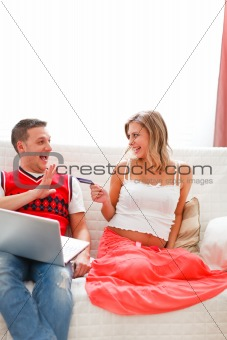 Happy pregnant woman with husband shopping on Internet