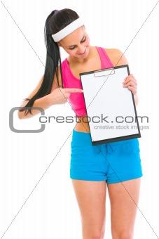 Slim girl pointing on blank clipboard