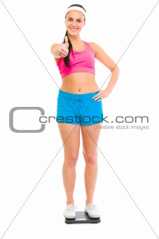 Fitness female standing on weight scale and showing thumbs up
