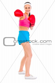 Fitness girl in boxing gloves punching