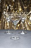 Three Martini glasses in front of glitter background
