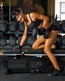 Beautiful woman is doing exercises with the bar