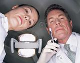 Low angle view of dentist and assistant with syringe