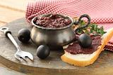 appetizer of olives, tapenade on a wooden board