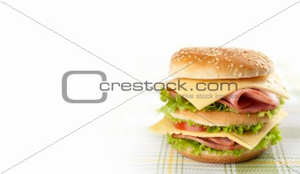 Big sandwich with lettuce, tomato, ham and cheese. Hamburger