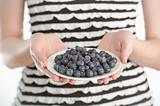 Young woman holding a plate with blueberries