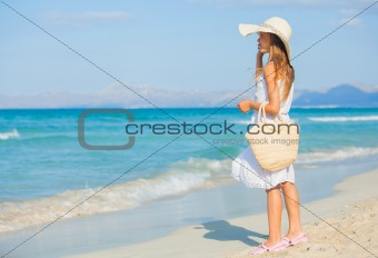 Adorable girl wearing elegant hat on the beach