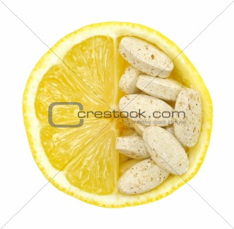 Close up of lemon and pills isolated - vitamin concept