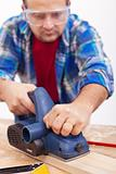 Man working wood with electric planer