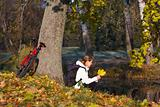 Woman cyclist relaxing in autumn park