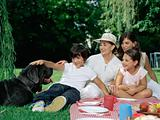 Family having picnic with their pet dog