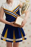 Cheerleader carrying a trophy