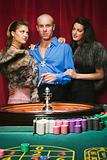 Women with wealthy man at roulette table