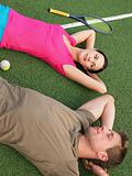 Young couple lying on tennis court