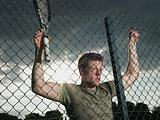 Tennis player behind wire fence