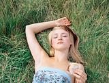 Woman holding cake and lying on the grass