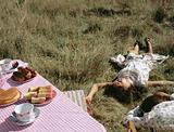 Couple lying in field near table