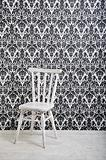 white wooden chair against vintage wallpaper