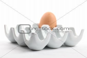 Ceramic egg holder with brown chicken egg