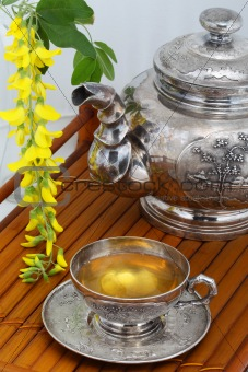 Green tea in a cup, flowers, yellow acacia on a bamboo tray