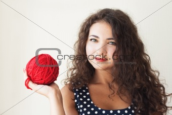 A beautiful young brunette with a ball of thread in their hands
