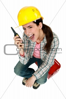Female construction worker yelling into a walkie-talkie