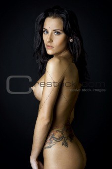 Back of the beautiful naked woman with tattoo.