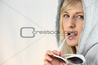 Woman with a hood on and chewing on her sunglasses