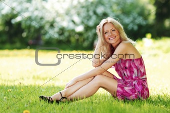 blonde sitting on green grass