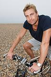 Man with a mountain bike on beach