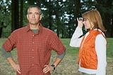 Woman looking at husband with binoculars