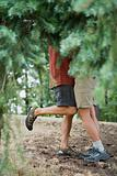 Couple embracing behind a tree