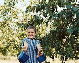 Boy carrying two baskets of fruit