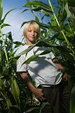Boy standing between corn plants