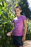Girl standing next to corn plants