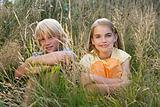 Children sitting in overgrown grass