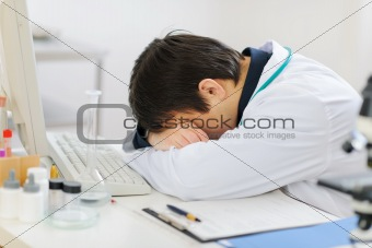 Tired medical doctor sleeping on keyboard
