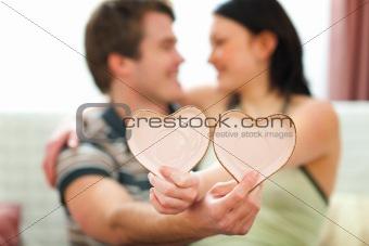 Closeup on Valentines hearts in hands of romantic couple