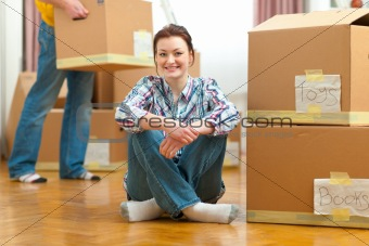 Portrait of girl and boyfriend carrying boxes to new house in background