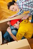 Smiling girl trying to pack boyfriend in cardboard box