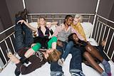 Partygoers relaxing on bed