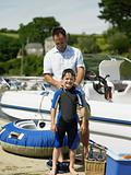 Father dressing son in wet suit