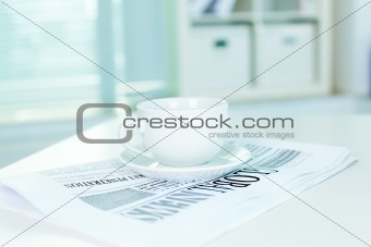 Cup and business newspaper