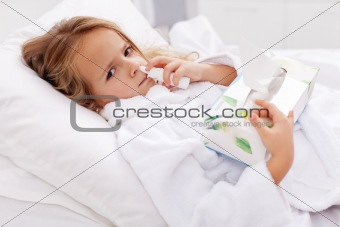 Little girl with bad cold - using nasal spray and paper napkins