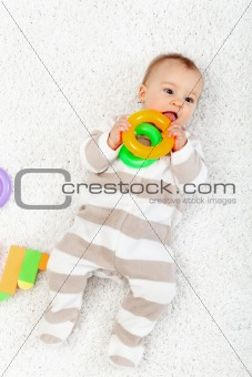 Baby girl playing on the floor chewing toys