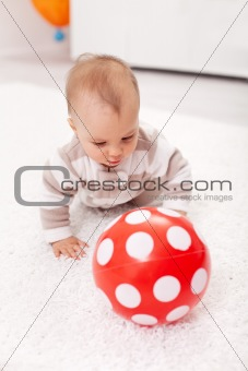 Baby girl chasing a red ball