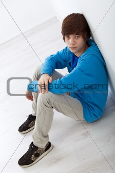 Teenager boy sitting on the floor by the wall